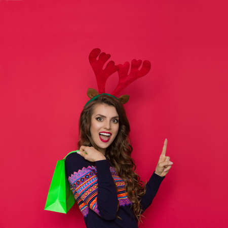 Excited young woman in sweater with colorful pattern and christmas reindeer horns holding green shopping paper bag, pointing up and talking. Waist up studio shot on red background.