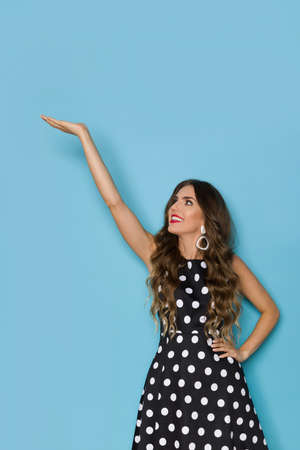Young woman in elegant black cocktail dress in polka dots pattern is holding hand raised, presenting something and looking up. Three quarter length studio shot against blue background. Foto de archivo
