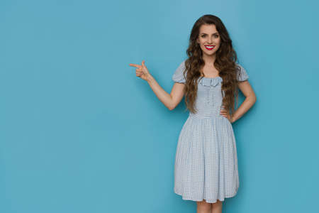 Beautiful young woman in blue checked dress is pointing at the side and smiling. Three quarter length studio shot on blue background.