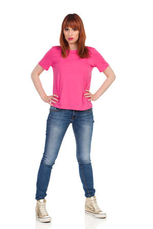Confused young woman in pink t-shirt, jeans and gold sneakers is standing, holding hands on hip and looking at camera. Front view. Full length studio shot isolated on white.