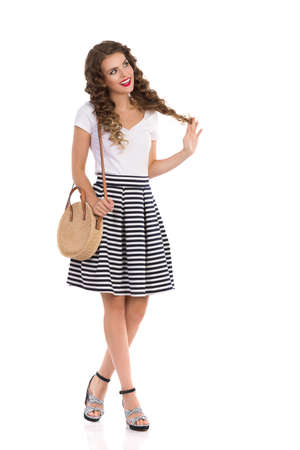 Happy beautiful young woman in striped, skirt, high heels and white top is walking with straw bag and looking away. Full length studio shot isolated on white. Foto de archivo