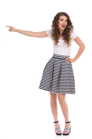 Excited beautiful young woman in striped mini skirt, white top and high heels is standing, pointing away and talking. Front view. Full length studio shot isolated on white.
