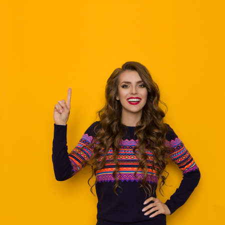 Happy young woman in sweater with colorful pattern is pointing up, looking at camera and talking. Waist up studio shot on yellow background.