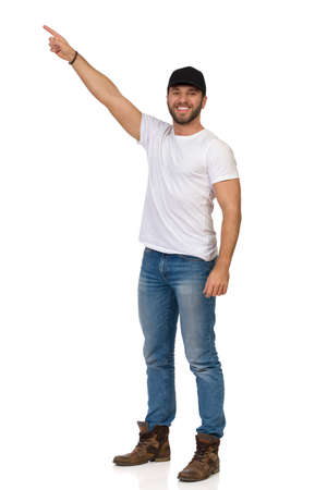 Smiling handsome casual man wearing black cap is standing, looking at camera and pointing up. Full length studio shot isolated on white.