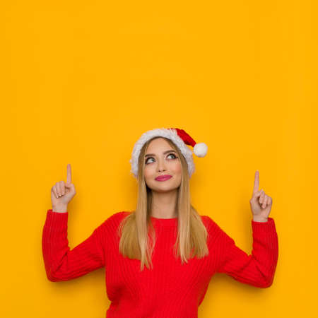Cute young woman in santa hat and red sweater is pointing up, looking and smiling. Waist up studio shot on yellow background.