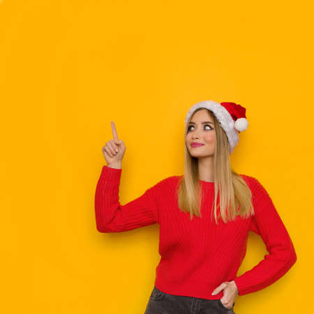 Young smiling woman in santa hat and red sweater is pointing, looking up and smiling. Waist up studio shot on yellow background.