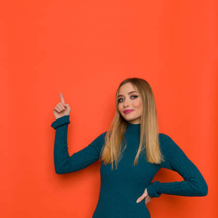 Cheerful young woman in teal sweater is pointing up and looking at camera. Waist up studio shot on orange background