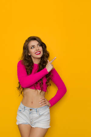 Beautiful young woman in a short pink sweater and jeans shorts is pointing, looking away and smiling. Three quater length studio shot on yellow background.