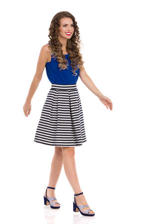 Beautiful young woman is walking in high heels, striped skirt and blue top, looking away and smiling. Side view. Full length studio shot isolated on white.