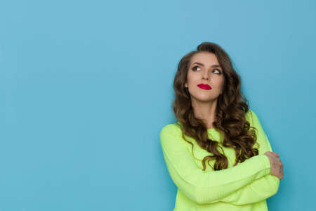 Pensive young woman in neon lime green sweater is holding arms crossed, looking up and thinking. Waist up studio shot on blue background.