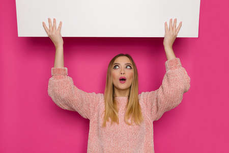 Surprised young woman in pink sweater is holding white banner over head, looking up and talking. Front view. Waist up studio shot on pink background.