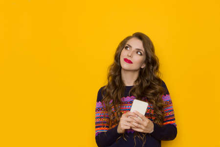 Thinking young woman in sweater with colorful pattern is holding telephone and looking away. Waist up studio shot on yellow background.
