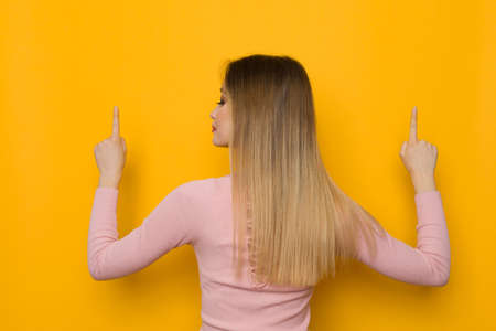 Young woman in pink sweater is pointing up and looking at the side. Rear view. Waist up studio shot on yellow background.