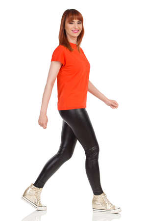 Casual young woman in orange t-shirt, black leather pants and gold sneakers is walking, looking at camera and smiling. Side view. Full length studio shot isolated on white.