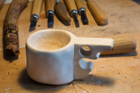 Handmade wooden mug kuksa with chisels in the background. Standard-Bild