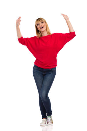 Beautiful happy woman in red sweater and jeans is holding arms raised, dancing and singing. Front view. Full length studio shot isolated on white. Standard-Bild