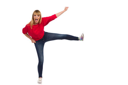 Casual young woman in red sweater, jeans and colorful sneakers is kicking and shouting. Front view. Full length studio shot isolated on white. Standard-Bild