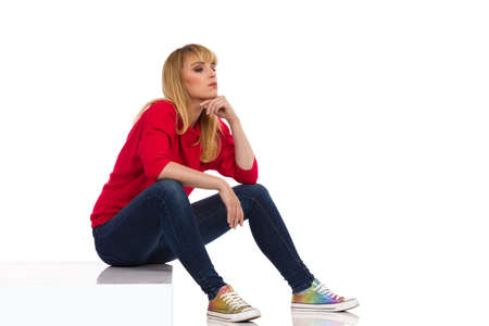 Bored young woman in red sweater is sitting on a step, holding hand on chin and looking away. Side view. Full length studio shot isolated on white. Standard-Bild