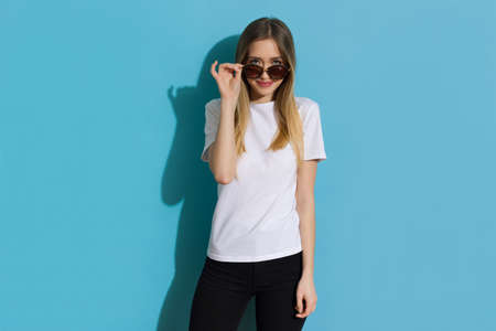 Cute happy young blond woman in white shirt is looking at camera over sunglasses. Three quarter length studio shot on blue background.
