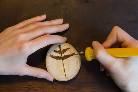 Female hands burn out a tree twig sign with soldering iron on wooden disc.