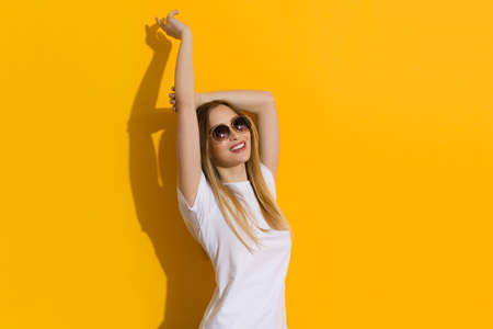Smiling young blond woman in white shirt and sunglasses is standing with arms raised against yellow sunny wall. Waist up stuido shot.
