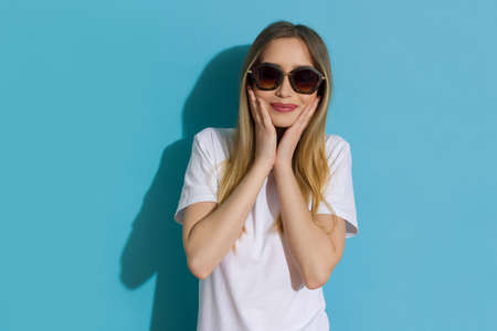 Excited young woman in white shirt and sunglasses is holding head in hand and smiling. Waist up studio shot on blue background.