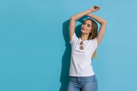 Relaxed young blond woman in white shirt and jeans is standing with arms raised against blue sunny wall and looking away. Three quarter length shot.