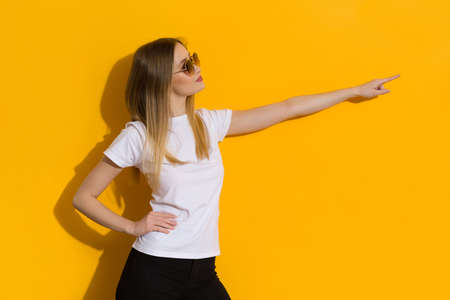Casual young woman in white shirt, and sunglasses is directing and looking aside. Waist up studio shot on yellow background. Standard-Bild