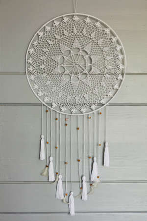 Lacy white dream catcher hanging on gray door. Standard-Bild