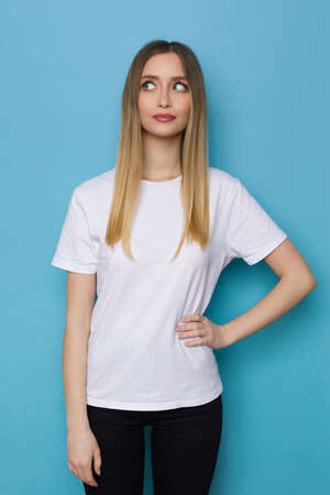 Serious young woman in whte shirt is holding hand on hip and looking aside. Three quarter length studio shot on blue background. Standard-Bild