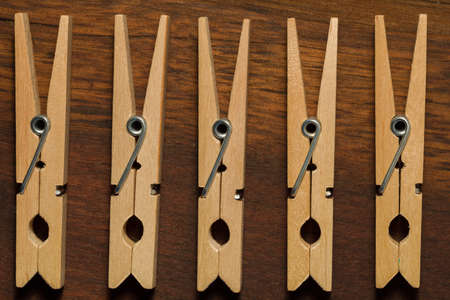 Five wooden clothes pegs lying on a dark table. Top View.