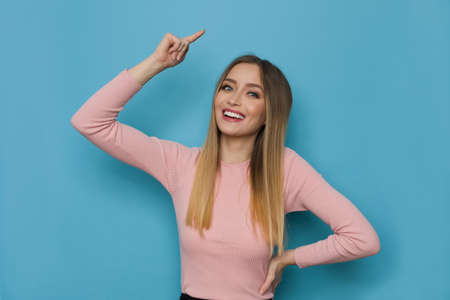 Happy young woman in pink sweater is pointing over head. Front view. Waist up studio shot on blue background.