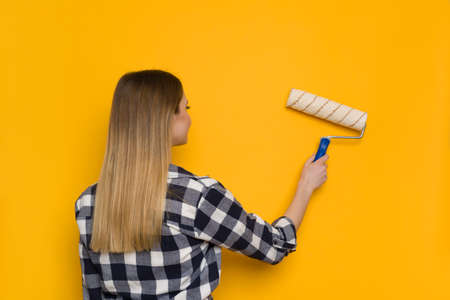 Young woman in lumberjack shirt is painting yellow wall with paint roller, rear view. Waist up shot.