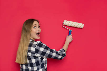 Happy young woman in lumberjack shirt is painting red wall with paint roller, looking at camera over the shoulder and shouting. Waist up shot.