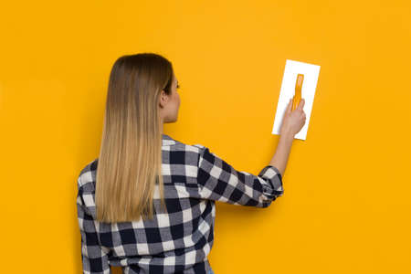 Young Blond Woman In Lumberjack Shirt Is Posing With Finishing Trowel On Yellow Wall. Rear View. Waist Up Shot. Concept photo. Standard-Bild
