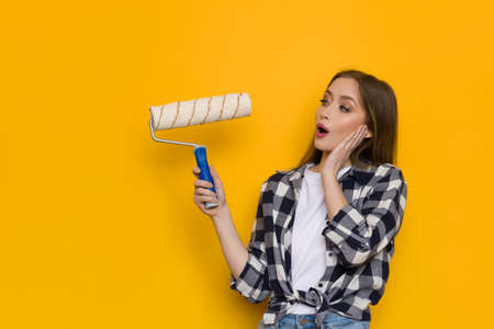 Surprised young blond woman in lumberjack shirt is holding paint roller, looking away and talking. Waist up shot on yellow background