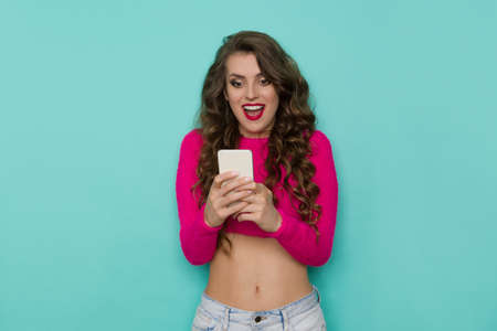 Excited young woman in a short pink sweater holds telephone and looks at the screen. Waist up studio shot on turquoise background.