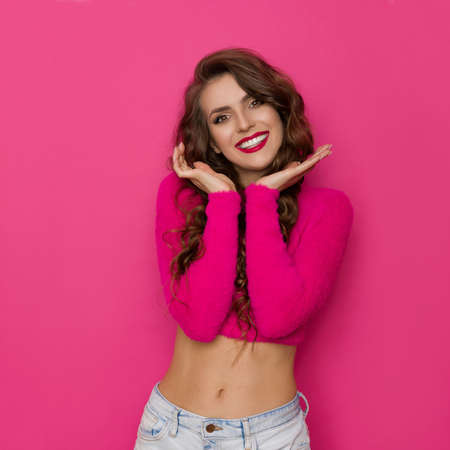Cute woman in a short pink sweater is holding head in hands, looking at camera and smiling. Waist up studio shot on pink background. Standard-Bild