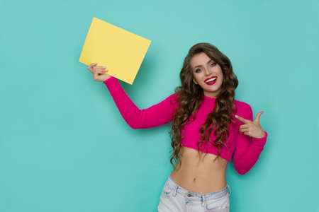 Beautiful young woman is holding yellow sheet of paper, pointing at it and smiling. Front view. Waist up studio shot on turquoise background. Standard-Bild