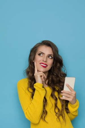 Young woman in yellow sweater is holding telephone, biting lip, looking away and thinking. Waist up studio shot on blue background. Standard-Bild