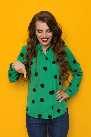 Smiling young woman in green shirt in black dots is looking down and pointing. Three quarter length studio shot on yellow background.