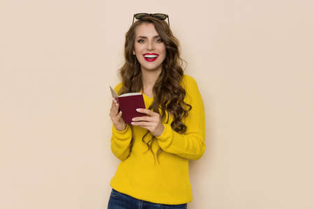 Happy young woman in yellow sweater holds open red passport, looks at camera and talks. Waist up studio shot on beige background.