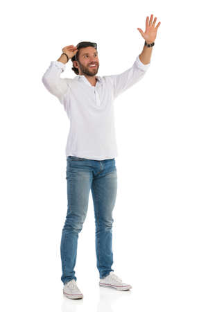Casual happy man in white shirt, jeans and sneakers is standing, looking up, holding hand raised and waving. Front side view. Full length studio shot isolated on white.