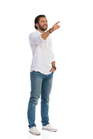 Casual happy man in white shirt, jeans and sneakers is standing with hand in pocket, looking away and pointing. Front side view. Full length studio shot isolated on white.