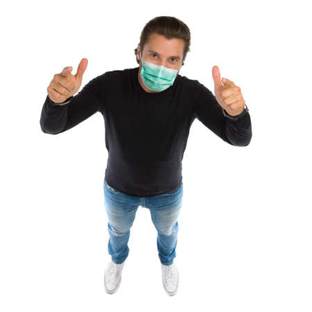 High angle view of standing man, wearing protective face mask, looking at camera and pointing. Full length studio shot isolated on white.