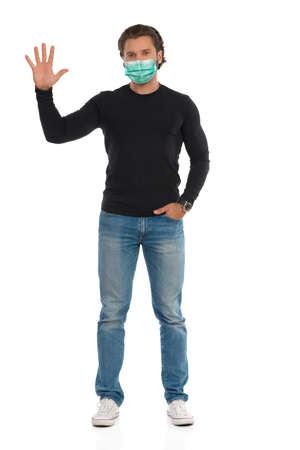 Casual handsome young man in protective face mask is standing with hand raised and showing open hand. Front view. Full length studio shot isolated on white.