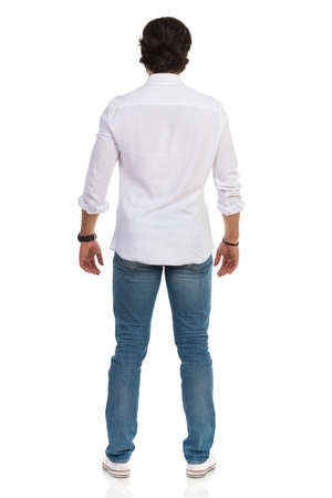 Casual man in jeans, sneakers and white shirt is standing relaxed. Rear view. Full length studio shot isolated on white. Standard-Bild