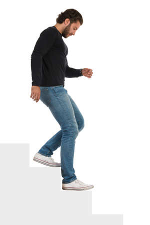 Casual serious young man in jeans, sneakers and black jersey is going down the stairs and looking away. Side view. Full length studio shot isolated on white.