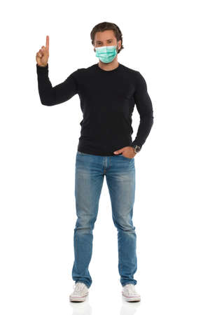 Casual handsome young man in protective face mask is standing with hand raised and pointing up. Front view. Full length studio shot isolated on white.