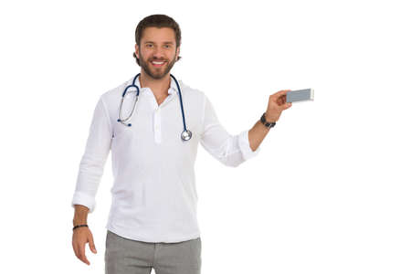 Handsome male doctor is holding small silver box in one hand, looking at camera and smiling. Front view. Three quarter length studio shot isolated on white. Standard-Bild